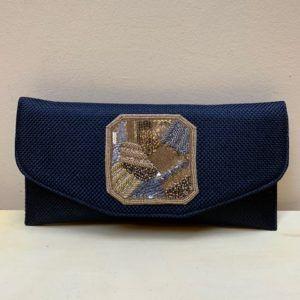 Bolso clutch con solapa y medallón bordado