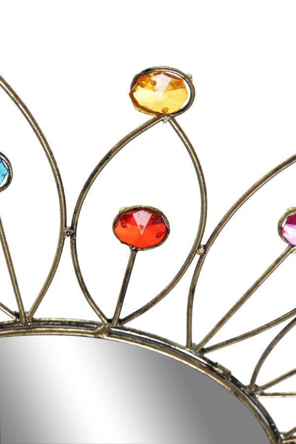 Espejo metálico con forma de sol y piedras de colores. Vista parcial