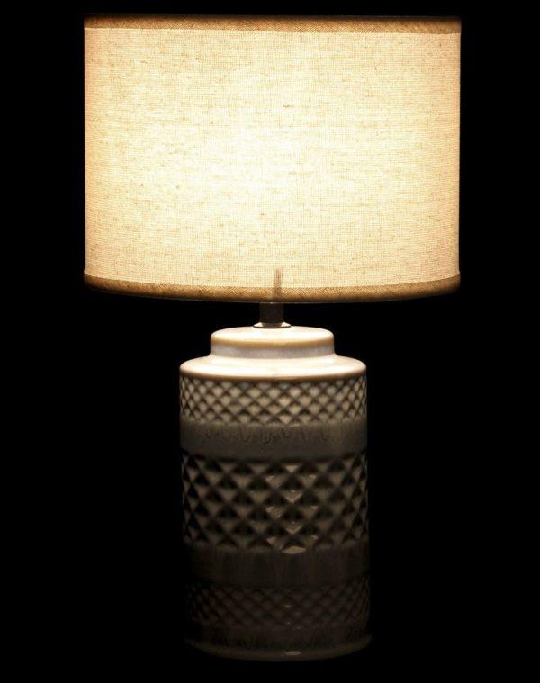 Lámpara de porcelana con pantalla cilíndrica. La de rombos encendida