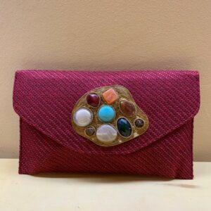 Cartera clutch con pieza irregular y motivos multicolor. Granate