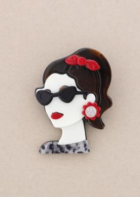 Broche pasta multicolores chica de perfil con gafas. Pelo negro