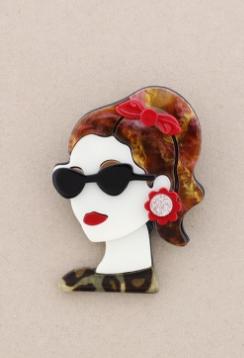 Broche pasta multicolores chica de perfil con gafas. Pelo caoba